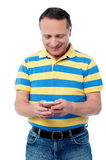Casual aged man using mobile phone Royalty Free Stock Photography