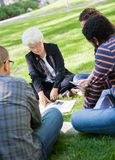 Casual Alternative Learning. Casual outdoor study group with female professor Royalty Free Stock Image
