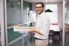 Casual architect smiling at camera holding blueprints Royalty Free Stock Photos