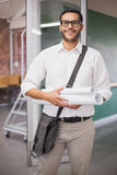 Casual architect smiling at camera holding blueprints Royalty Free Stock Images