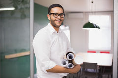 Casual architect smiling at camera holding blueprints Royalty Free Stock Photography