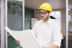Casual architect studying his blueprints Stock Photography