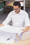 Casual architect studying his blueprints Royalty Free Stock Image