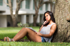 Casual Asian girl thinks while studying under a tree on school c Stock Photos