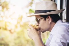 Casual Asian man drink hot coffee happily in nature royalty free stock images
