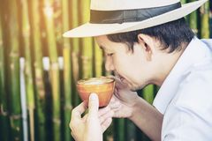 Casual Asian man drink hot coffee happily in nature royalty free stock image