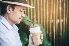 Casual Asian man drink ice coffee happily in nature stock photo