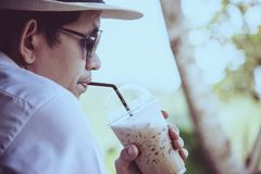 Casual Asian man drink ice coffee happily in nature royalty free stock image