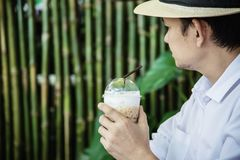 Casual Asian man drink ice coffee happily in nature royalty free stock images