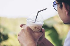 Casual Asian man drink ice coffee happily in nature stock image