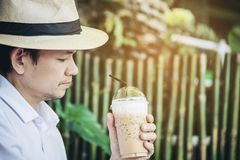 Casual Asian man drink ice coffee happily in nature royalty free stock photography