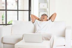 Casual asian man enjoying music. In livingroom Stock Images