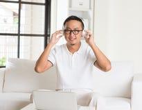 Casual asian man enjoying music. In livingroom stock photography
