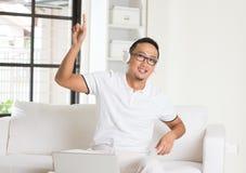 Casual asian man enjoying music. In livingroom stock photos