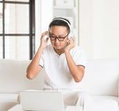 Casual asian man enjoying music. In livingroom royalty free stock photography