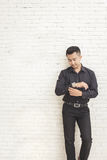 casual asian man standing while fixing his shirt sleeve Royalty Free Stock Photos
