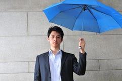 Casual Asian Man with umbrella. Smart casual asian man with blue umbrella Stock Photos