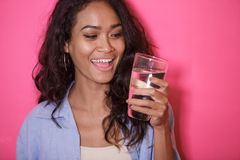 Casual asian woman with a glass of mineral water. Close up portrait of casual asian woman with a glass of mineral water on pink background Stock Photos