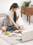 Casual asian woman having breakfast and working in home. Stock Images