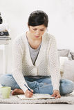 Casual asian woman sitting on the floor and working in home. Stock Photo