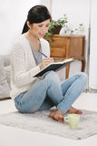 Casual asian woman sitting on the floor and working in home. Royalty Free Stock Image