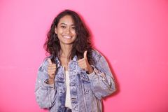 Casual asian woman smiling while giving thumbs up. Portrait of casual asian woman smiling while giving thumbs up on pink background Stock Photo