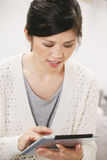 Casual asian woman working with digital tablet at home. Stock Photo