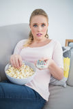 Casual astonished blonde holding remote and lying on couch Stock Images