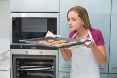 Casual attractive woman smelling baking tray with cookies. In bright kitchen royalty free stock image
