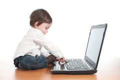 Casual baby typing on a laptop computer keyboard Royalty Free Stock Image