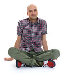 Casual bald man sitting with legs crossed Royalty Free Stock Image