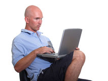 Casual Bald Man using Computer. This man is at home or at the beach connecting to his office or just surfing the web Royalty Free Stock Photography