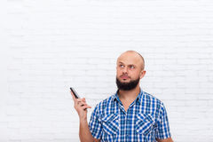 Casual Bearded Business Man Confused Doubtful Holding Cell Smart Phone Look At Copy Space Office Royalty Free Stock Photography