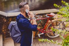 Bearded male in a park talks by smart phone. Casual bearded male in a park talks by smart phone royalty free stock image