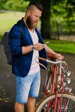 Bearded male in a park talks by smart phone. Casual bearded male in a park talks by smart phone stock images