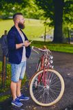 Bearded male in a park talks by smart phone. royalty free stock photography