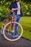 Image of a man on a retro bicycle. Casual bearded male in a park talks by smart phone stock images