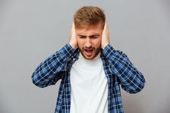 Casual bearded man covering his ears and shouting stock photo
