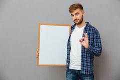 Casual bearded man holding blank board and showing ok gesture Royalty Free Stock Photos