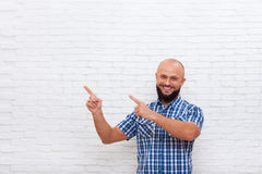 Casual Bearded Man Smiling Point Fingers Up To Copy Space Stock Photography