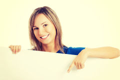 Casual beautiful woman pointing on copy space. Royalty Free Stock Photo