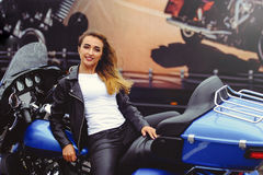 Casual beautiful woman sits on a big tourist motorcycle on the street bright smile on a sunny day.  Stock Photography