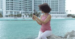 Casual black girl taking selfie on embankment. Side view of casual black girl sitting on rocky shore of tropical city river using smartphone and taking selfie stock video footage
