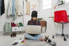 Casual blogger woman working in her fashion office. Young creative woman sitting in the floor with laptop stock photos