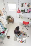 Casual blogger woman working in her fashion office. Young creative woman sitting in the floor with laptop royalty free stock image