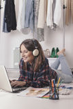 Casual blogger woman working with laptop in her fashion office. Young creative woman stretched in the floor and listening music stock photos