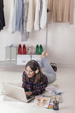 Casual blogger woman working with laptop in her fashion office. Young creative woman stretched in the floor and listening music royalty free stock photos