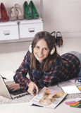 Casual blogger woman working with laptop and magazine in her fashion office. Young creative woman stretched in the floor and listening music stock photography