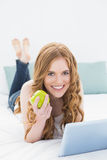 Casual blond using tablet PC while holding an apple in bed Stock Images