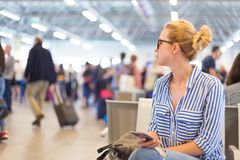 Woman using her cell phone while waiting to board a plane at departure gates at international airport. Stock Images